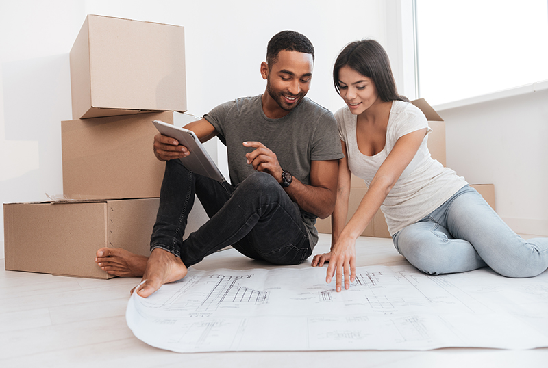 Couple planning decoration at new home sitting on the floor